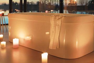 Badewanne mit brennenden Kerzen vor Fensterfront mit Abendstimmung