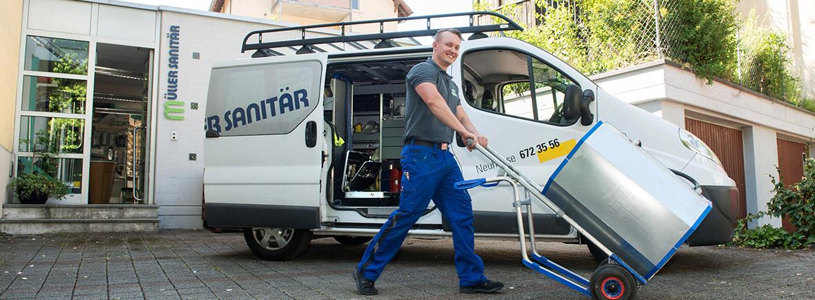 Servicemonteur mit Karre vor Lieferwagen